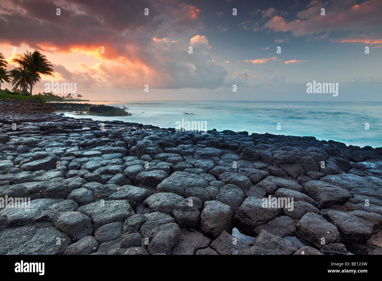 Basalt columns (columnar jointing) and sunrise, Poipu. Kauai, Hawaii. - Stock Image