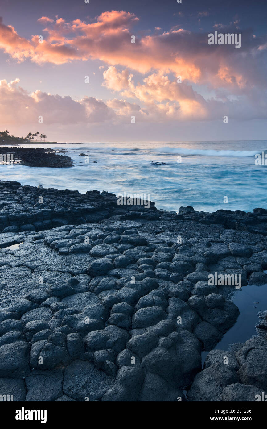 Basaltic columns (columnar jointing) and sunrise, Poipu. Kauai, Hawaii. - Stock Image