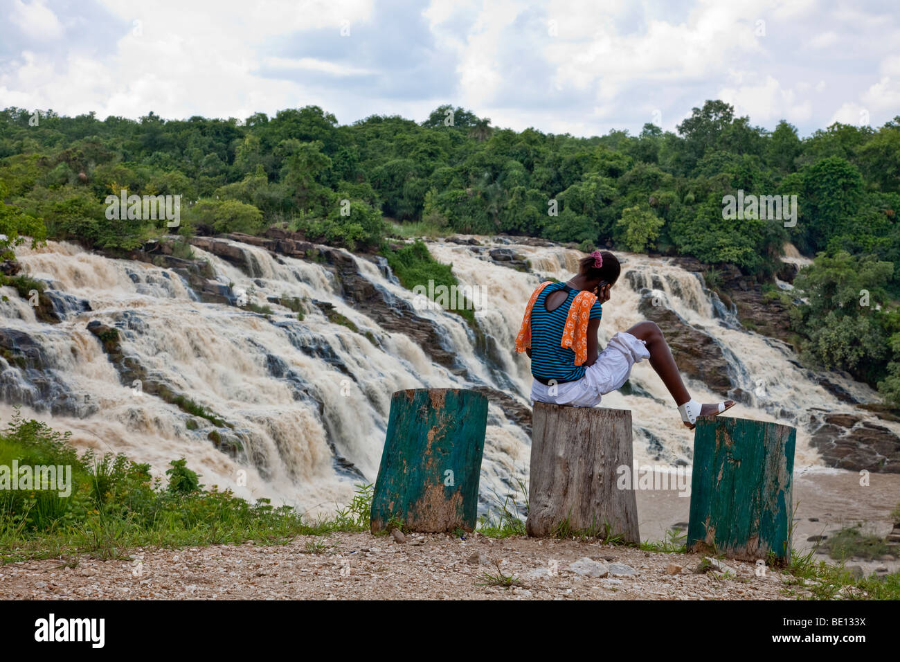 A woman chats on her cell phone while looking over the impressive Gurara Falls in Niger State, Nigeria. - Stock Image