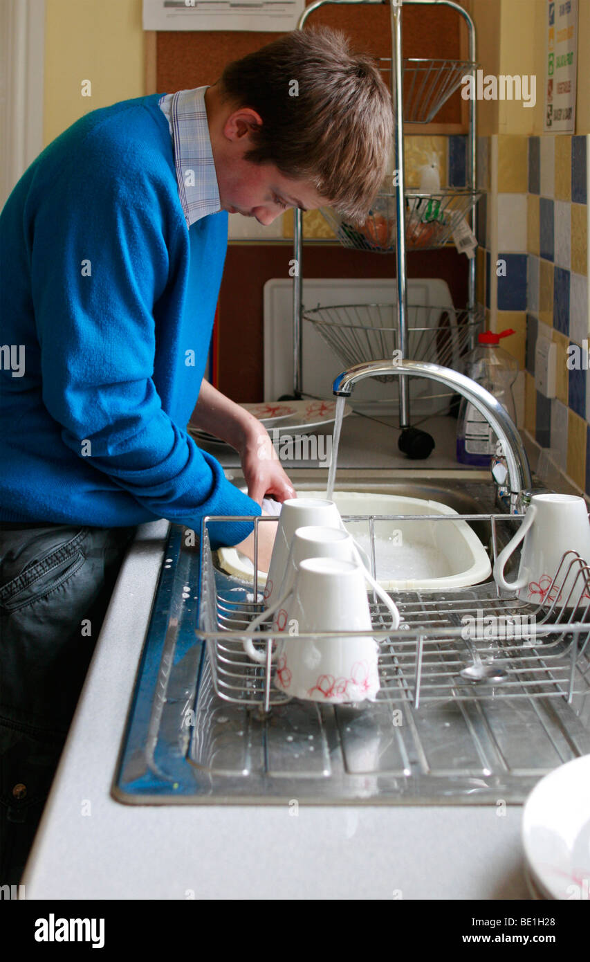 Barry-John, 18 and on the autistic spectrum doing the washing up - Stock Image