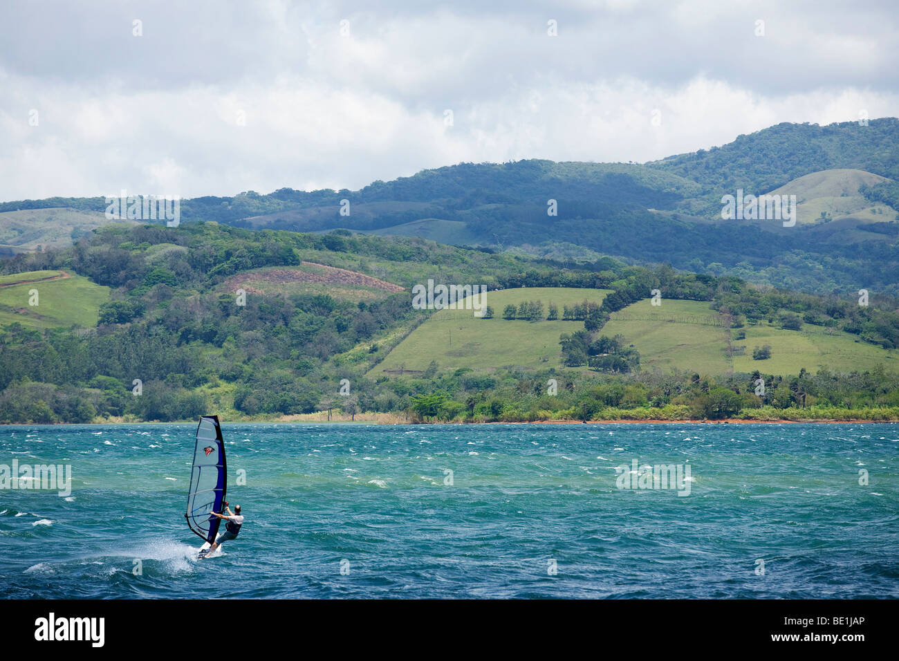 A wind surfer sails across Lake Arenal In Costa Rica - Stock Image