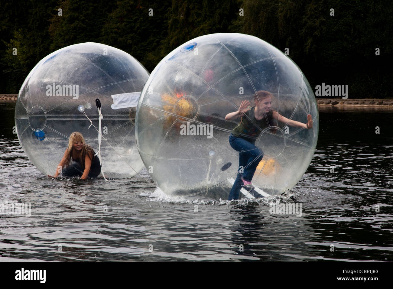 Two young girls playing inside a bubblerunner across the public lake at Rouken Glen park, Glasgow, UK, Scotland - Stock Image