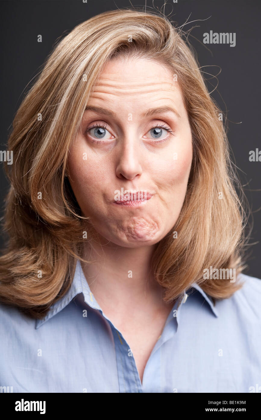 Blonde woman with quizzical facial expression - Stock Image