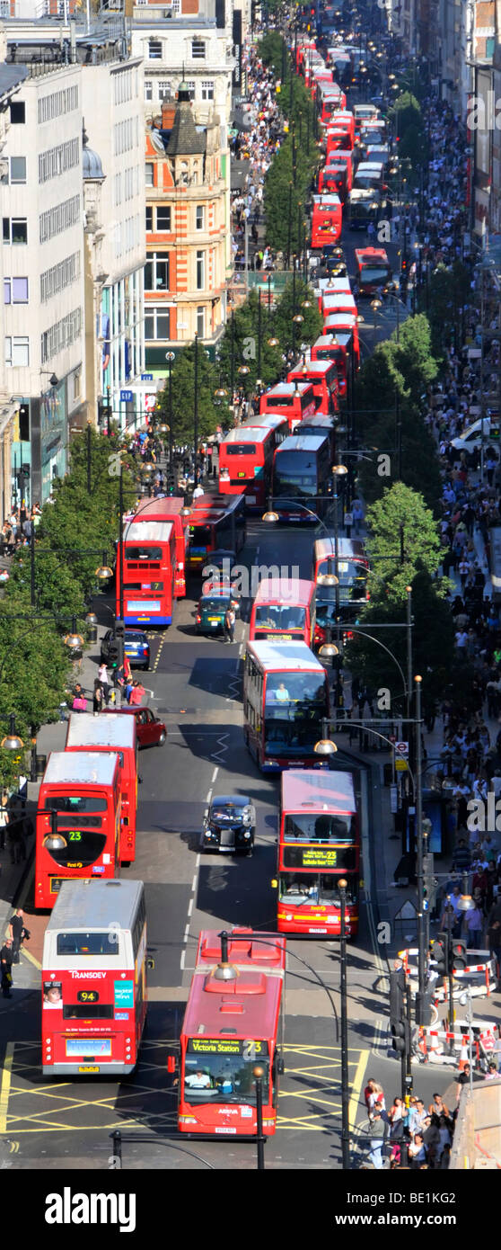 Looking down on UK London Oxford Street with shoppers & aerial views of long queues of double decker red London - Stock Image
