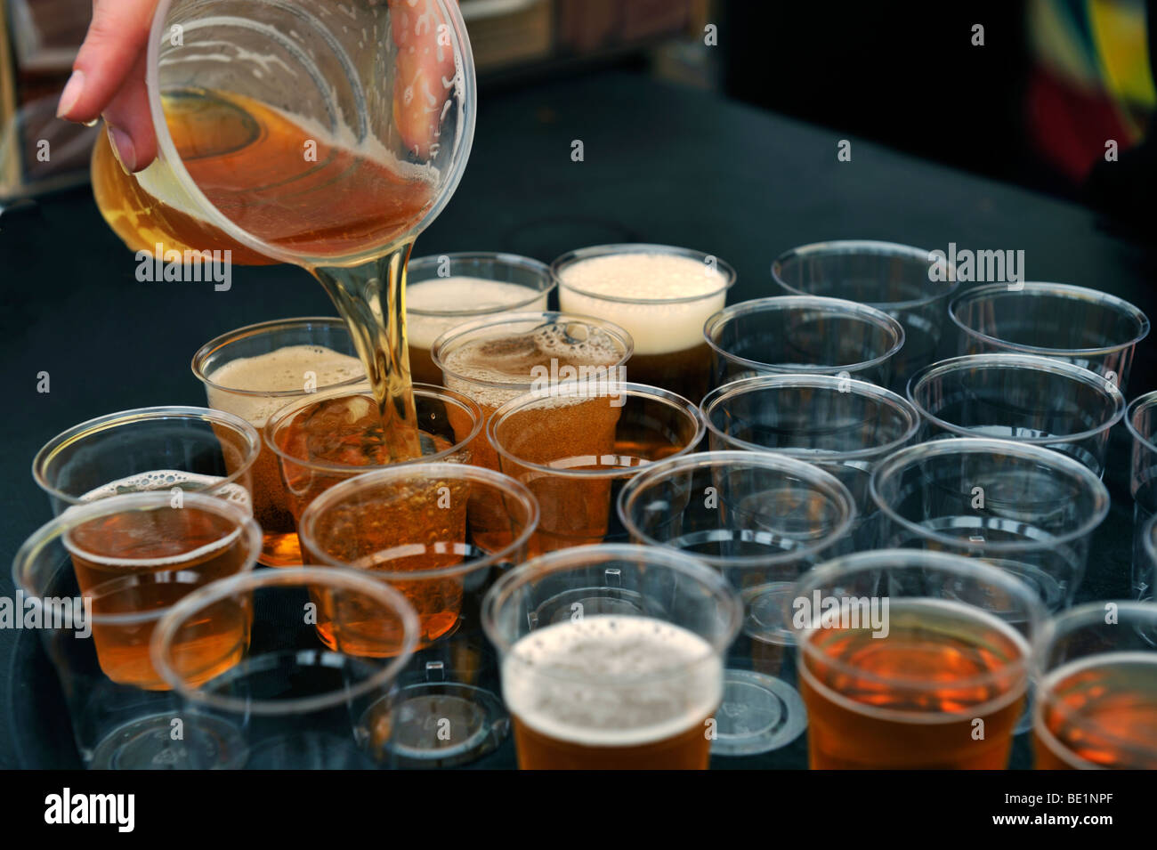 Pouring beer from pint glass into small sampling glasses - Stock Image