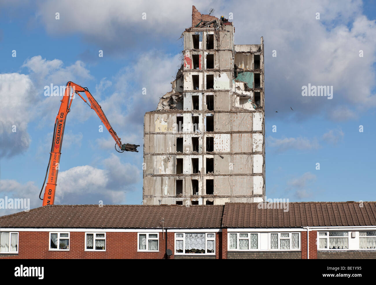A residential tower block being demolished behind a row of houses in Birmingham, England, UK. - Stock Image