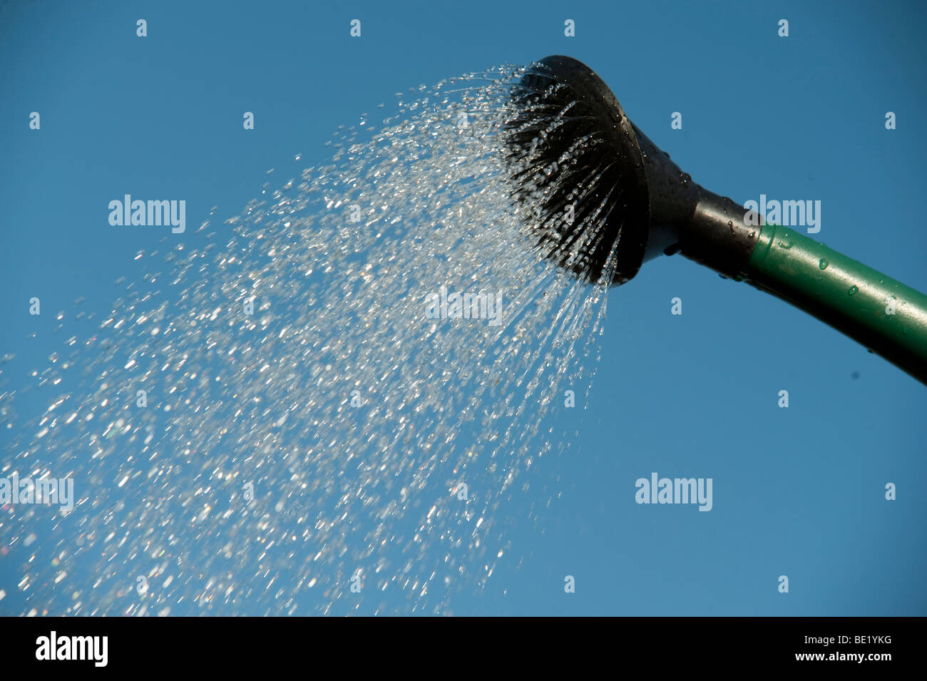 Water pouring from watering can spout against blue sky background sprinkling gardening tool - Stock Image