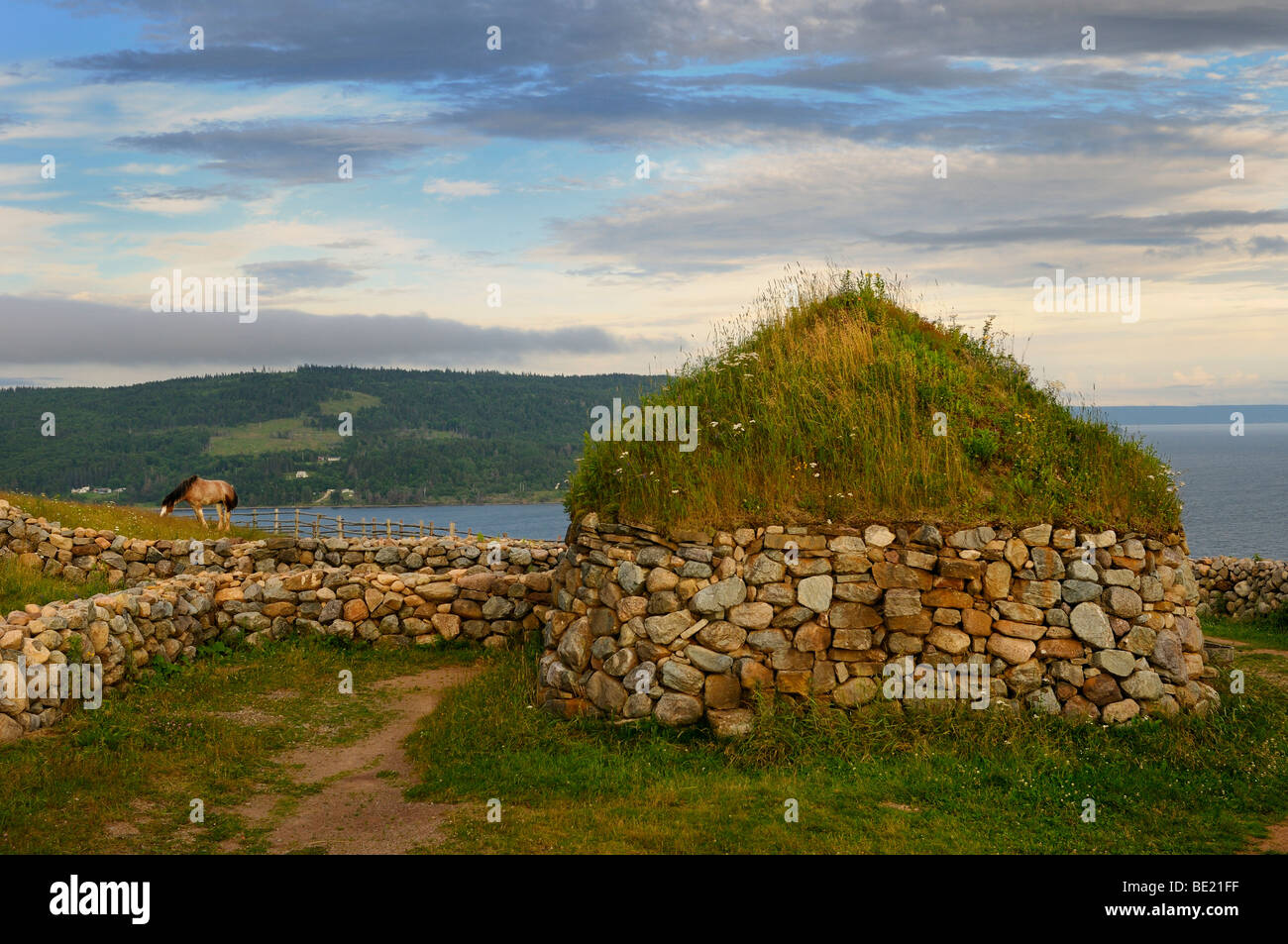 Clydesdale horse and Black House with sod roof and stone walls at Highland Village Museum Iona Cape Breton Island - Stock Image