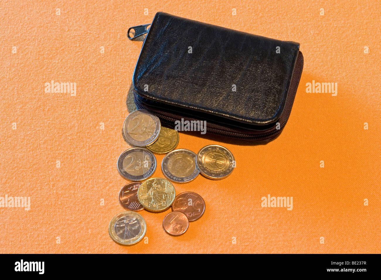 Half-open black leather purse with loose change spread out on an orange support. Porte-monnaie noir et menue monnaie. Stock Photo