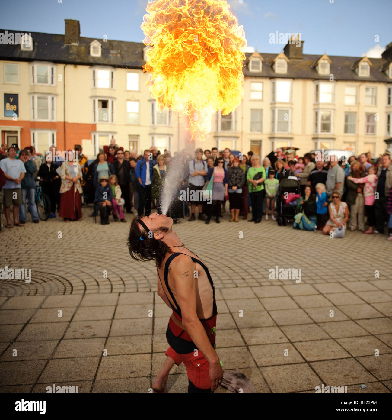 Fire Breather with De Propere Fanfare belgian marching band performing on the promenade, Aberystwyth Wales UK - Stock Image