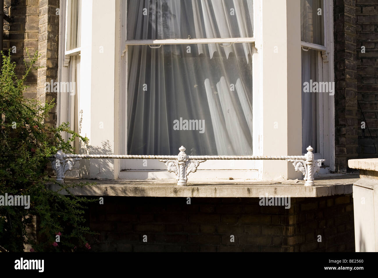 bay window with net curtains in sunshine - Stock Image