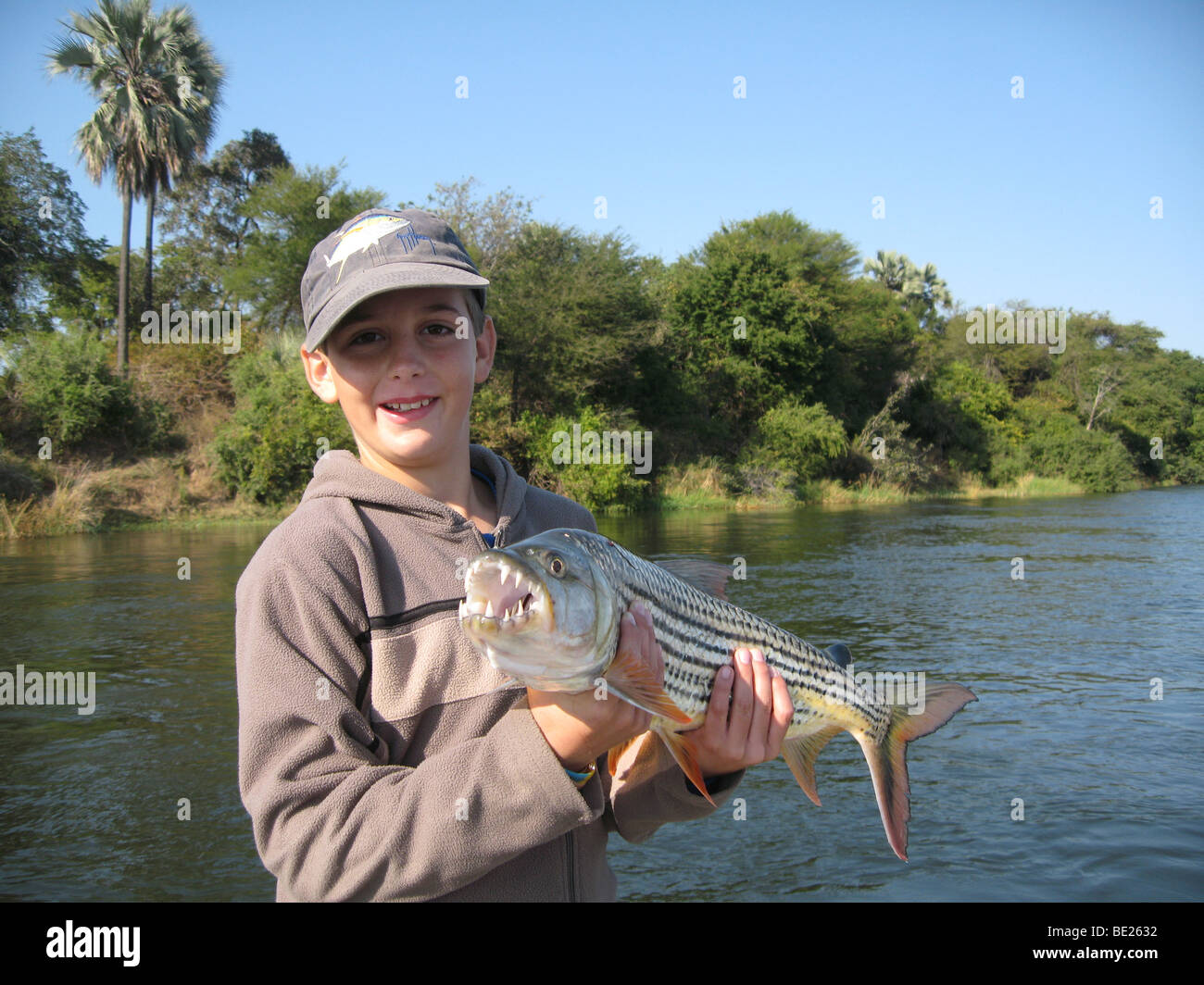 Young boy holding large tiger fish he has just caught Zambesi River Zambia - Stock Image