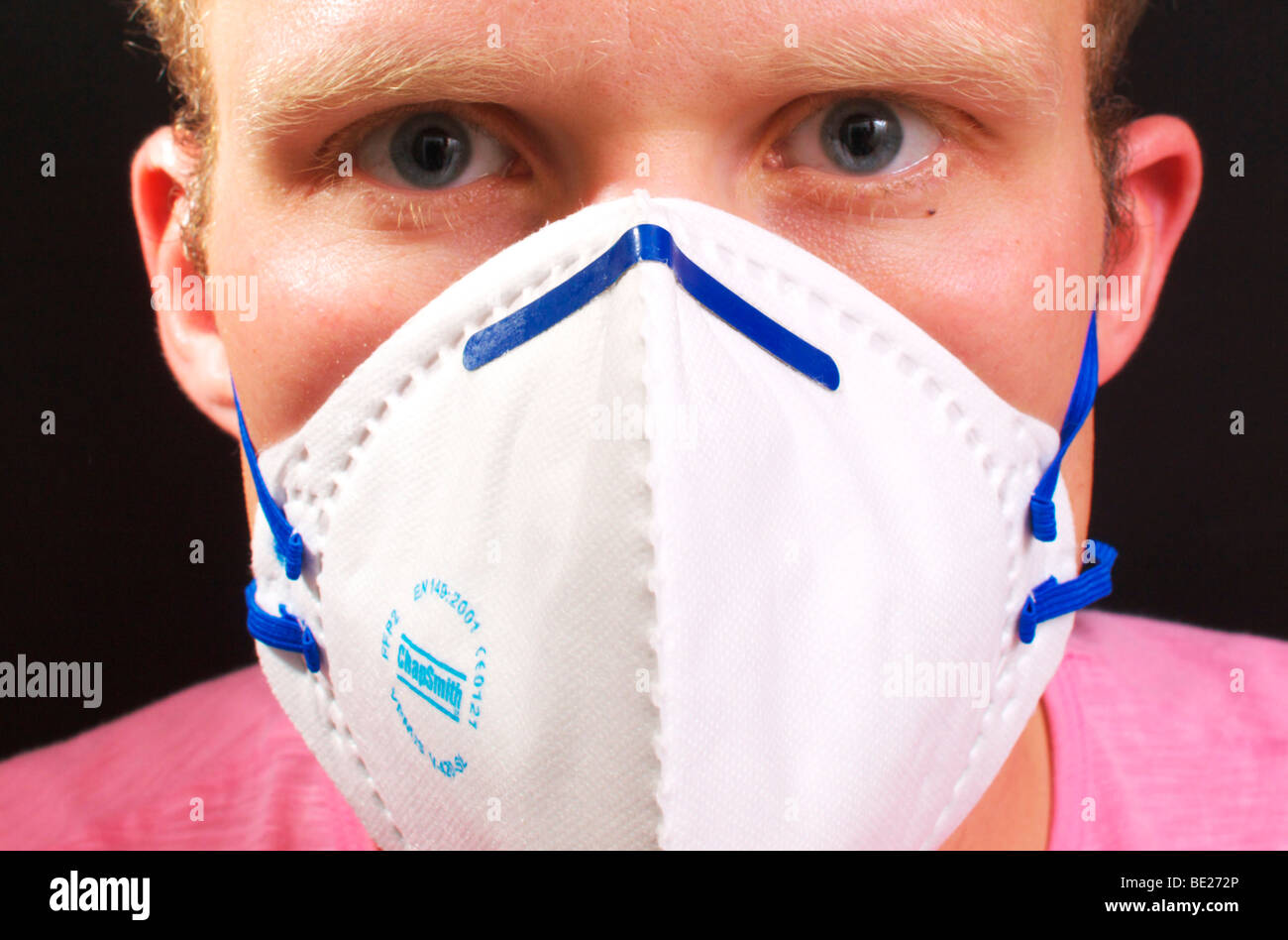 Young male wearing protective mask in the fight against swine flu - Stock Image