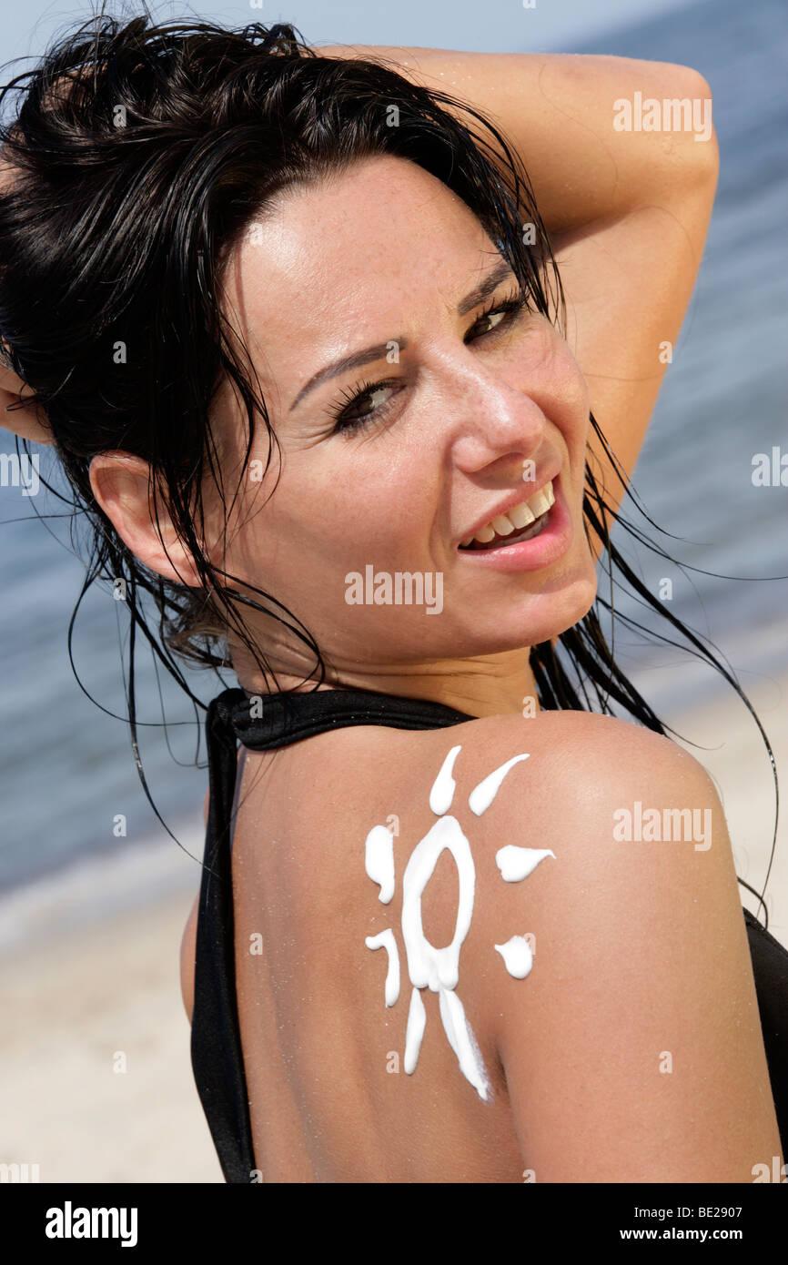 Portrait of attractive woman with sun-shaped sun cream - Stock Image