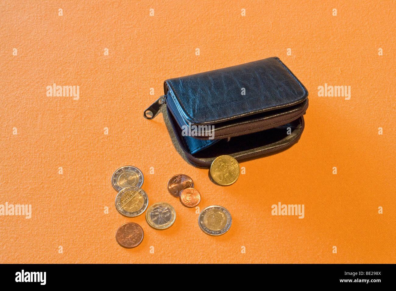 Half-open black leather purse with loose change spread out on an orange support. Porte-monnaie noir et menue monnaie. - Stock Image