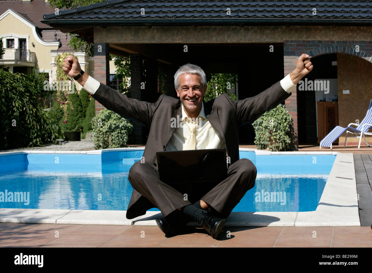 Happy businessman sitting next to the swimming pool Stock Photo
