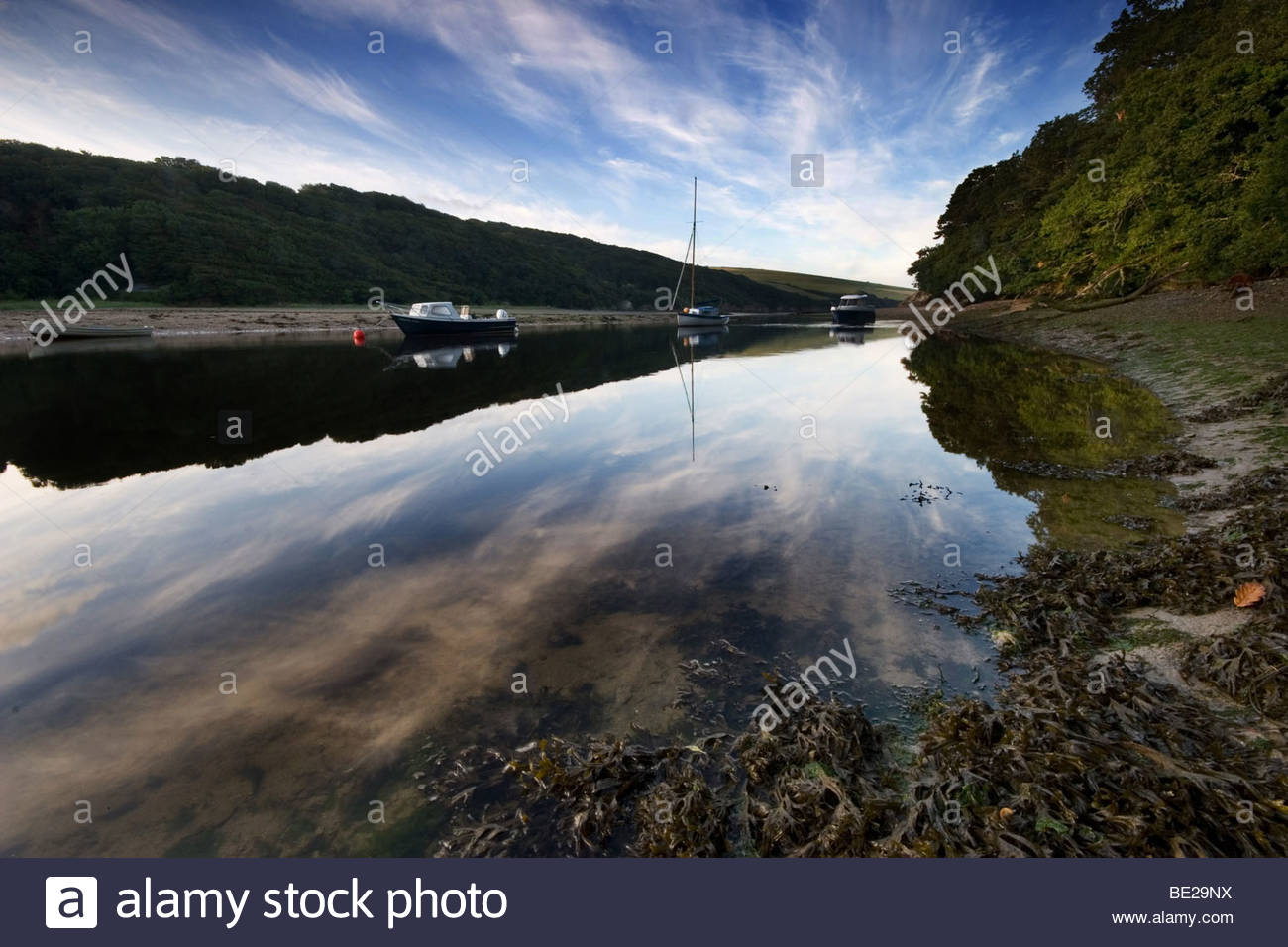 The early morning wispy clouds are reflected in the mirror like waters of the Erme estuary in Devon - Stock Image