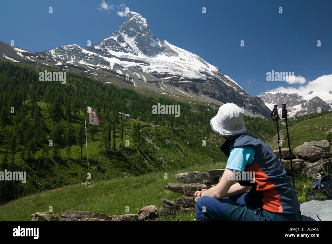 Hiker taking a rest facing Matterhorn, Swiss Alps - Stock Image