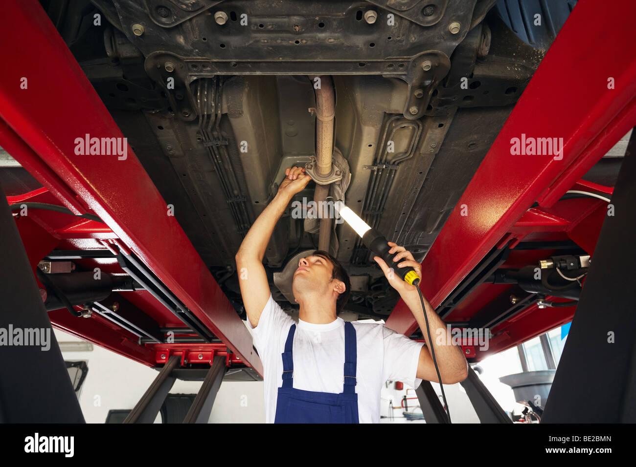 mechanic under car - Stock Image