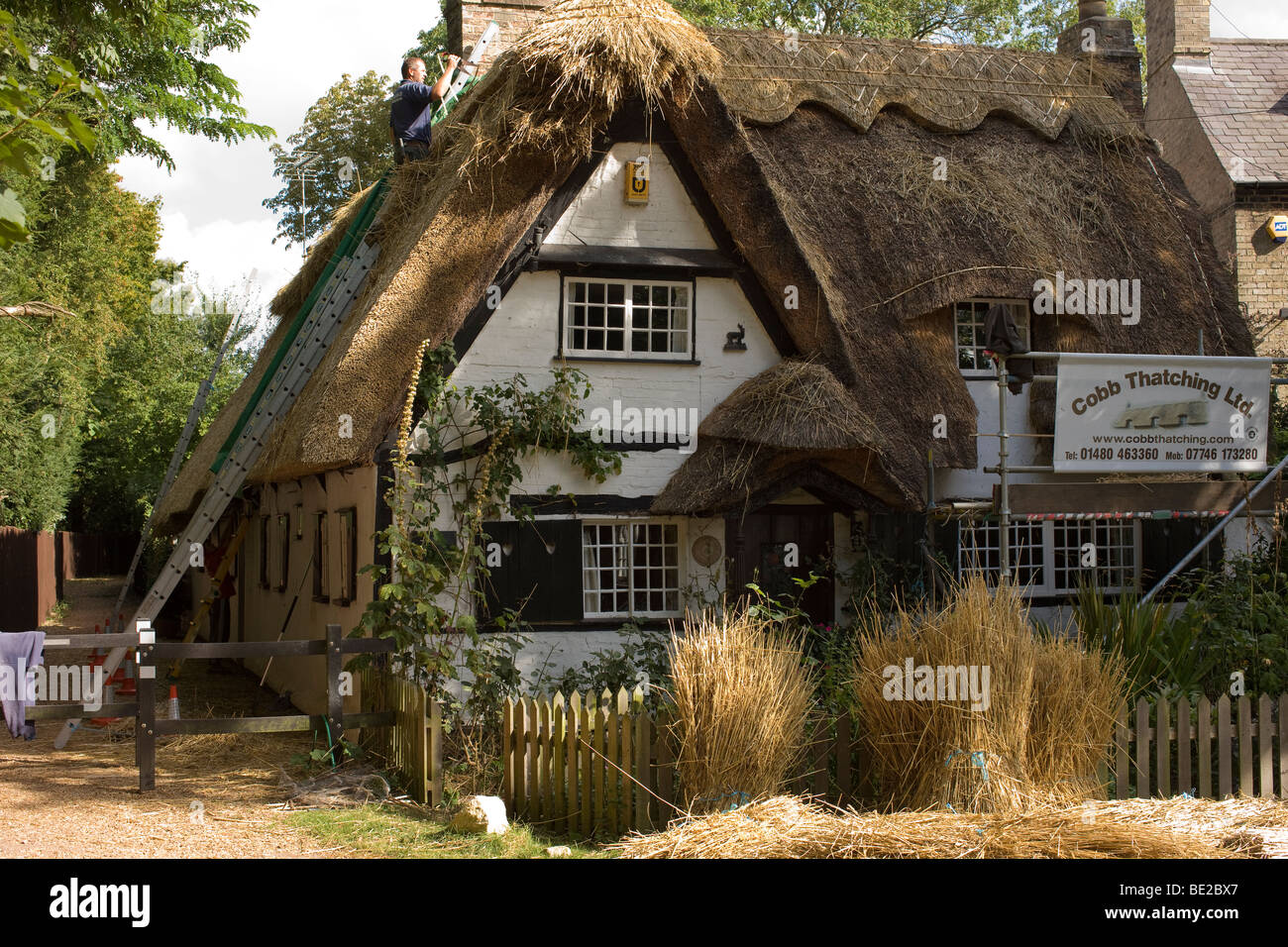 Cottage in the process of having thatch repaired with wheat straw. - Stock Image