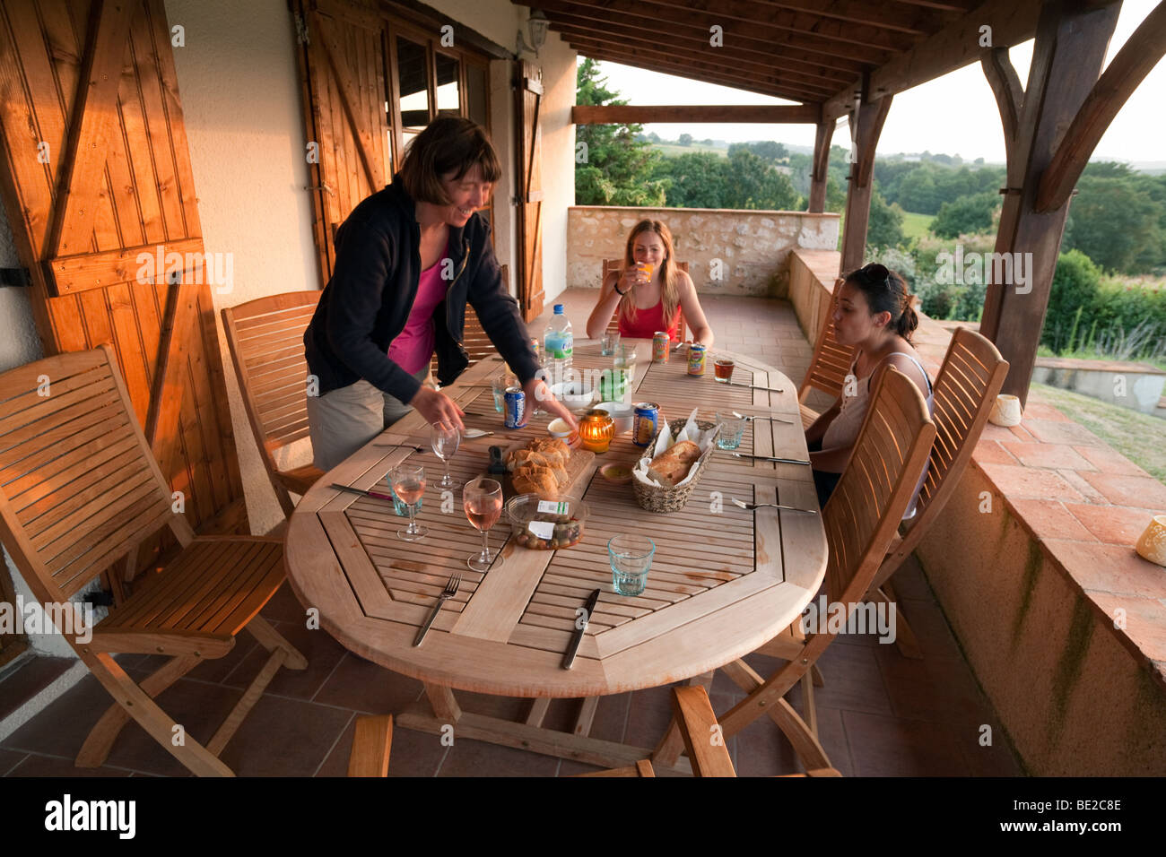 A family enjoying an evening meal on the veranda outdoors,  Aquitaine, France - Stock Image