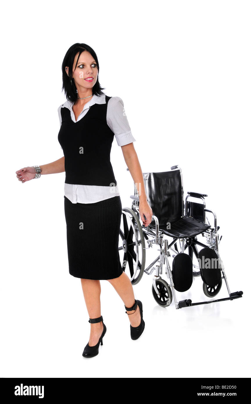 Young woman walking away from wheelchair isolated over a white background - Stock Image