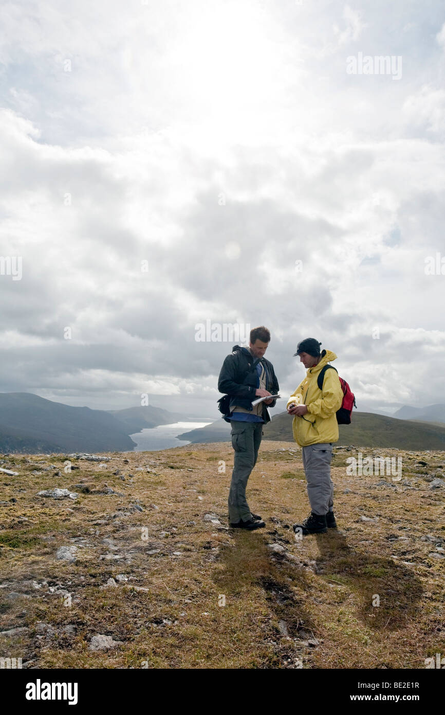 Two walkers consulting map. Cairngorm national park, Scotland - Stock Image