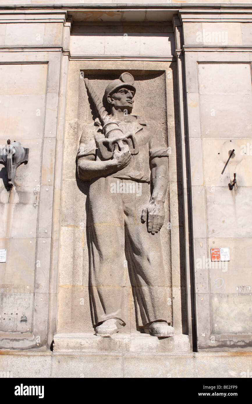 Warsaw Poland social realism figure of a miner worker from the 1950s on the side of the building in Plac Konstytucji - Stock Image