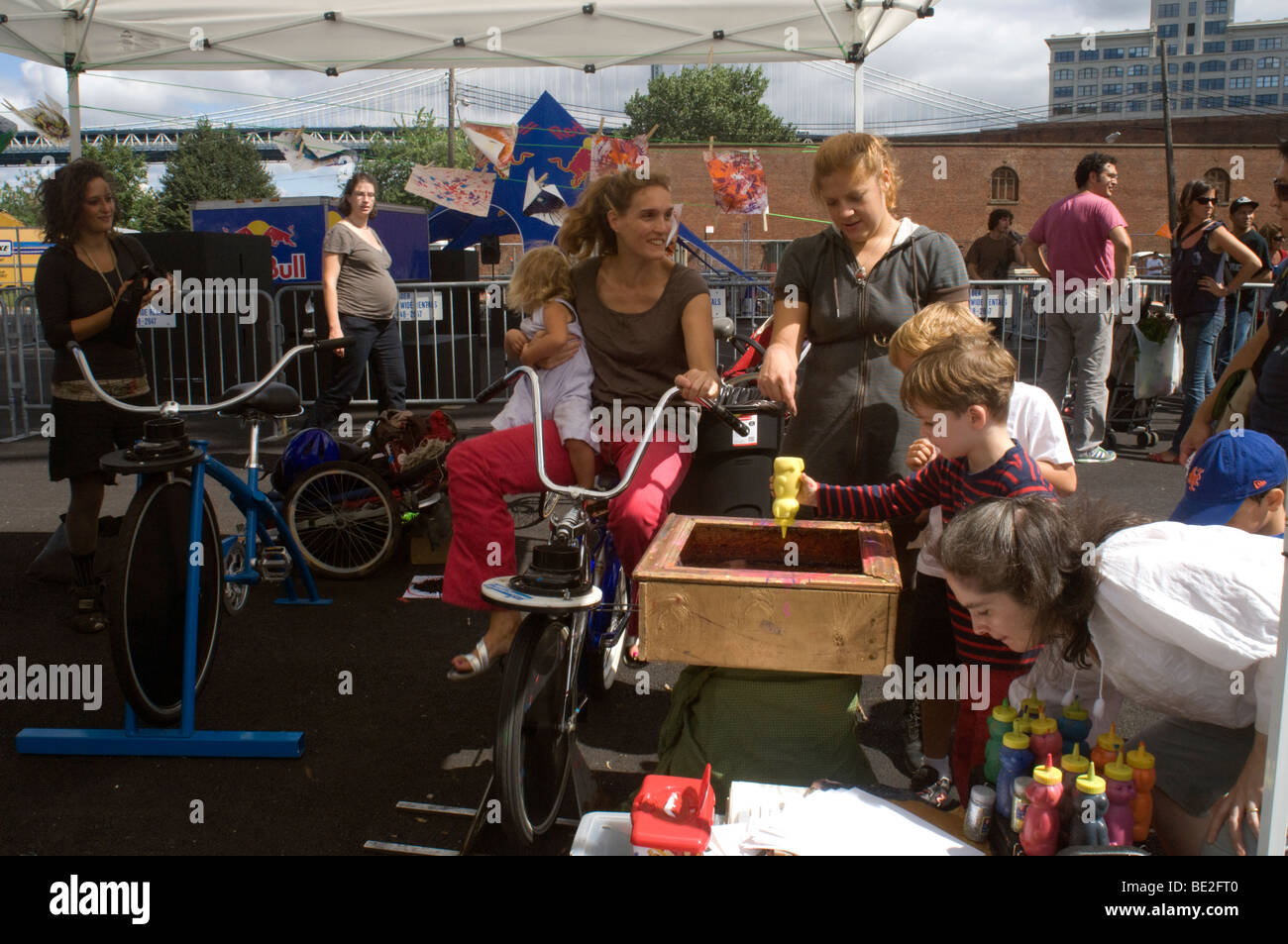Visitors peddle furiously on a Pedal Powered Spin Art bicycle to make spin art in Brooklyn in New York - Stock Image