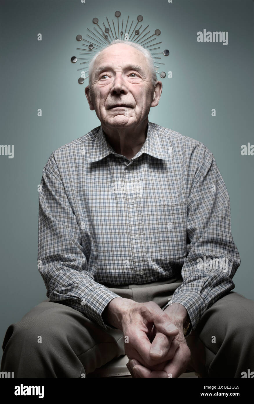An elderly man with a halo formed by a clock - Stock Image
