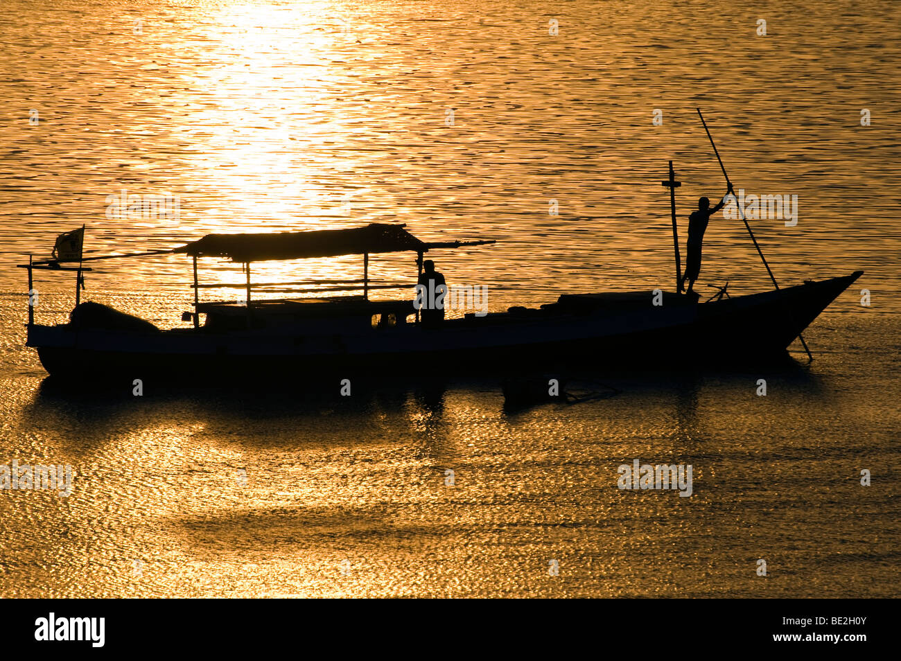 Fishermen back to the harbour at sunset - Stock Image