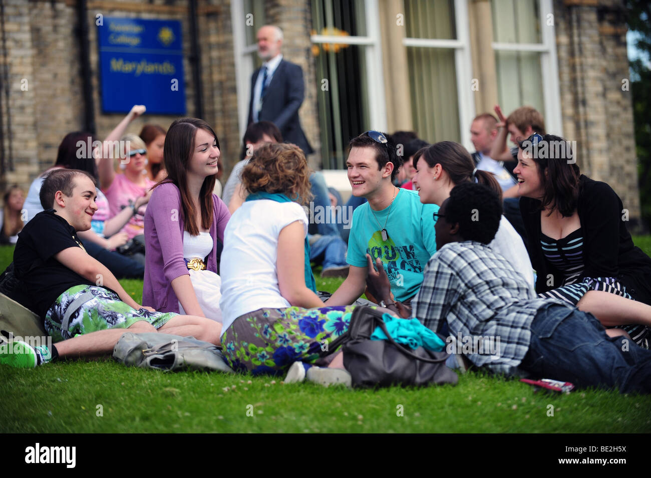 Students relax on grass during a break at a sixth form further education college - Stock Image