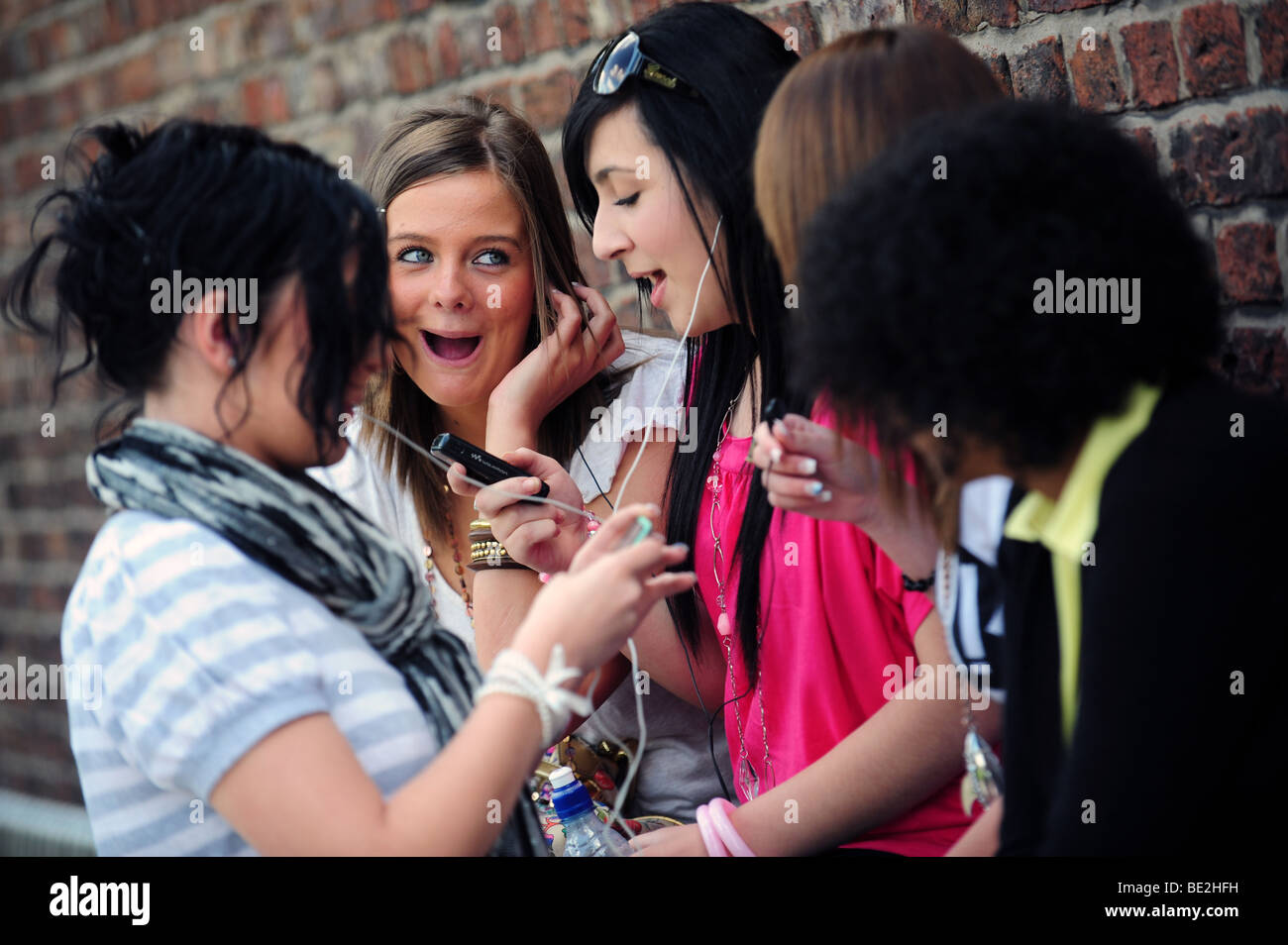Students listen to an i-pod during a break at a sixth form further education college - Stock Image