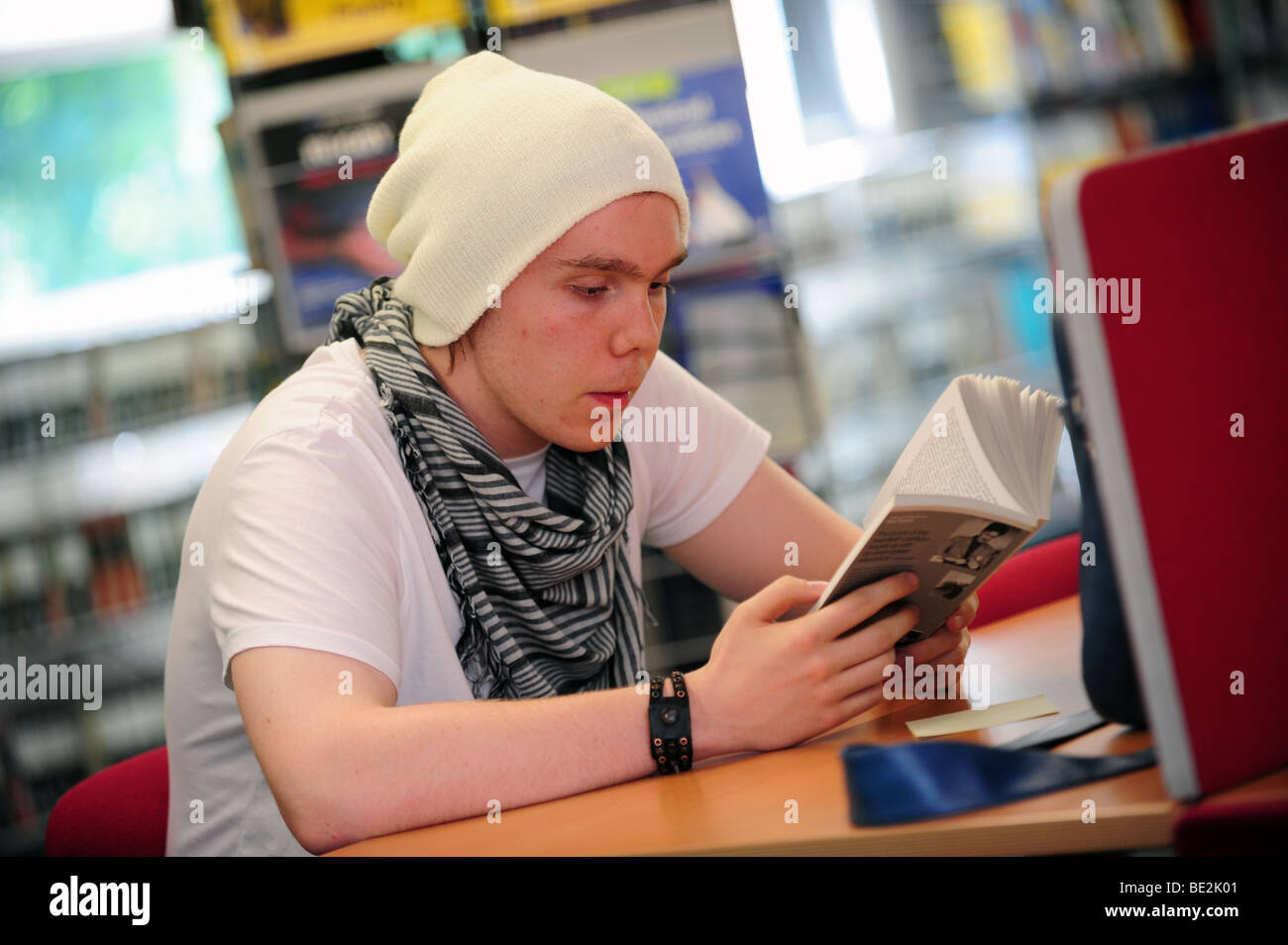 Student reads in library at sixth form further education college - Stock Image
