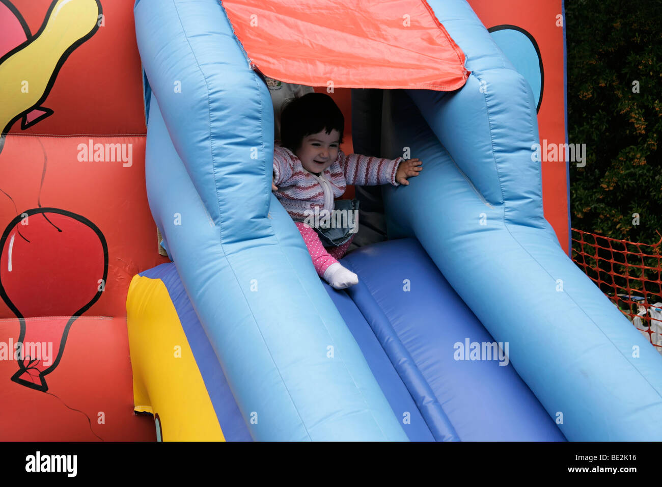 Toddler going down the slide of a bouncy castle, UK - Stock Image
