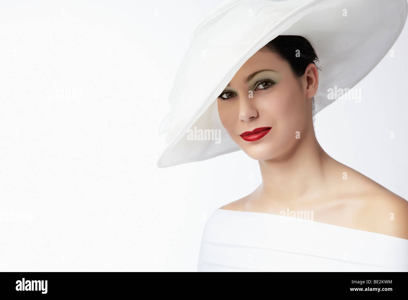 Portrait of a young woman wearing a white summer hat and white dress, looking directly towards the viewer - Stock Image