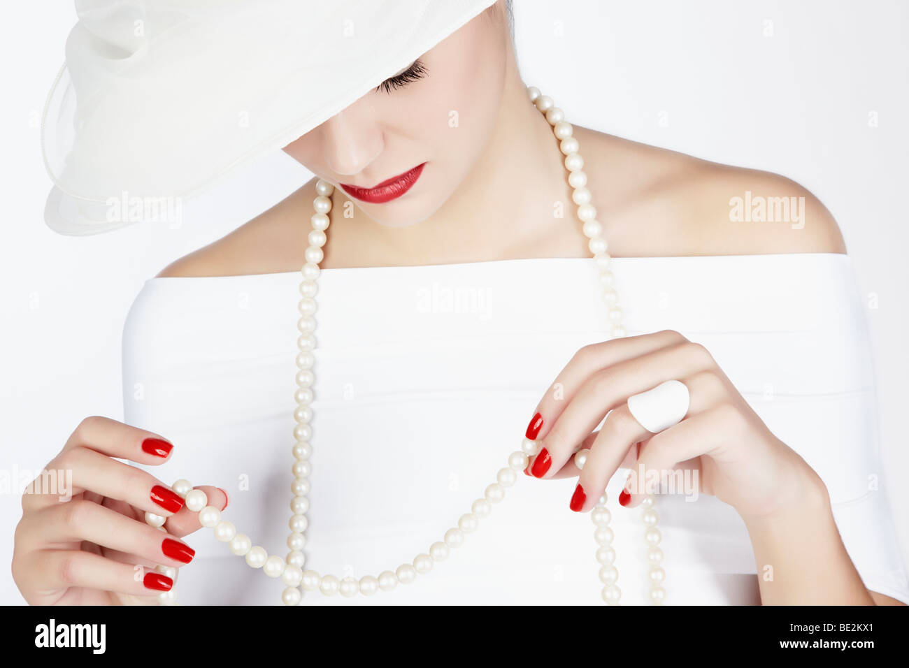 Portrait of a young woman wearing a white summer hat, a white dress and a pearl necklace - Stock Image