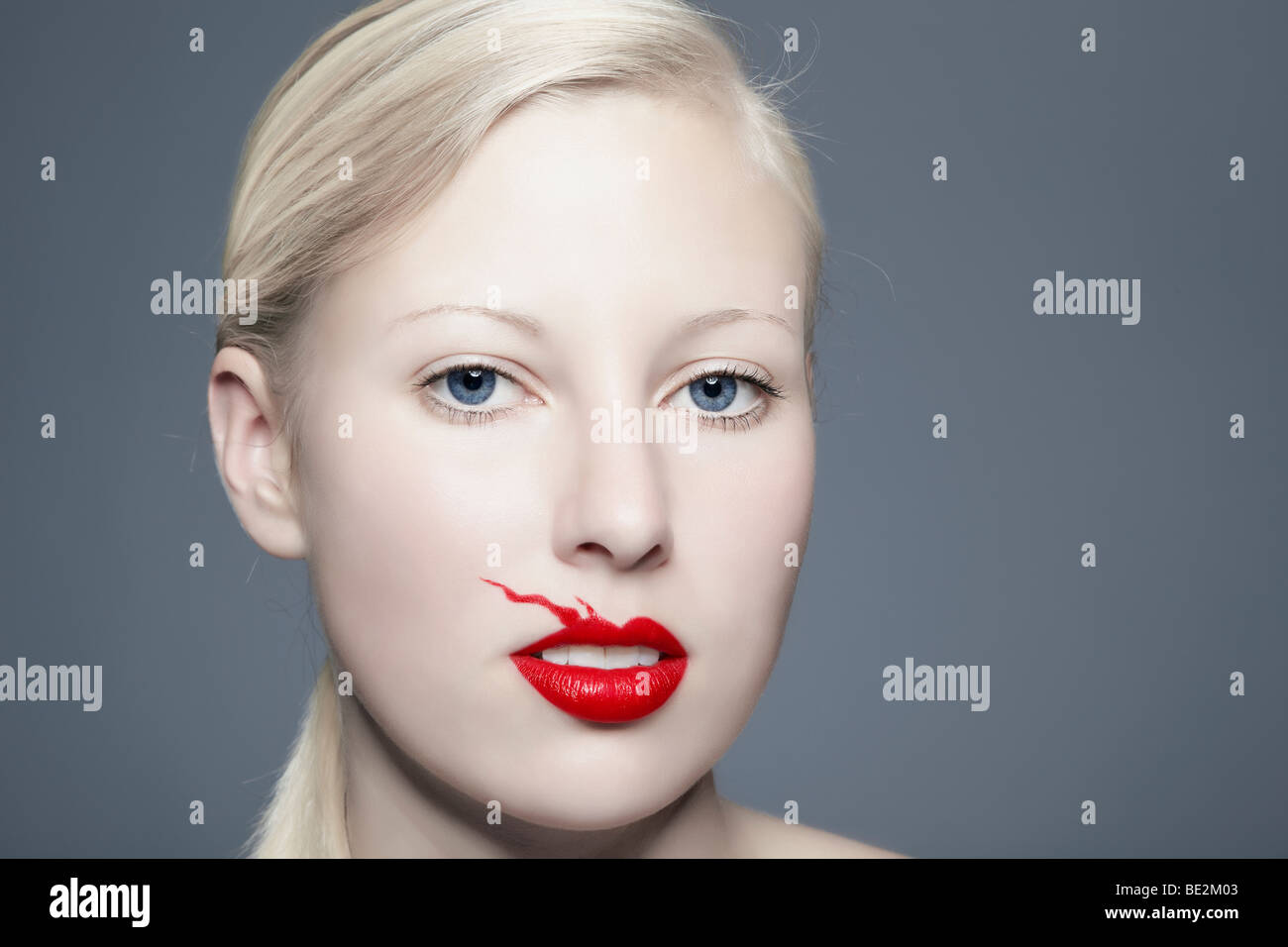 Portrait of a young blond woman with lipstick bleeding above her lip looking towards the viewer, imperfect, beauty - Stock Image