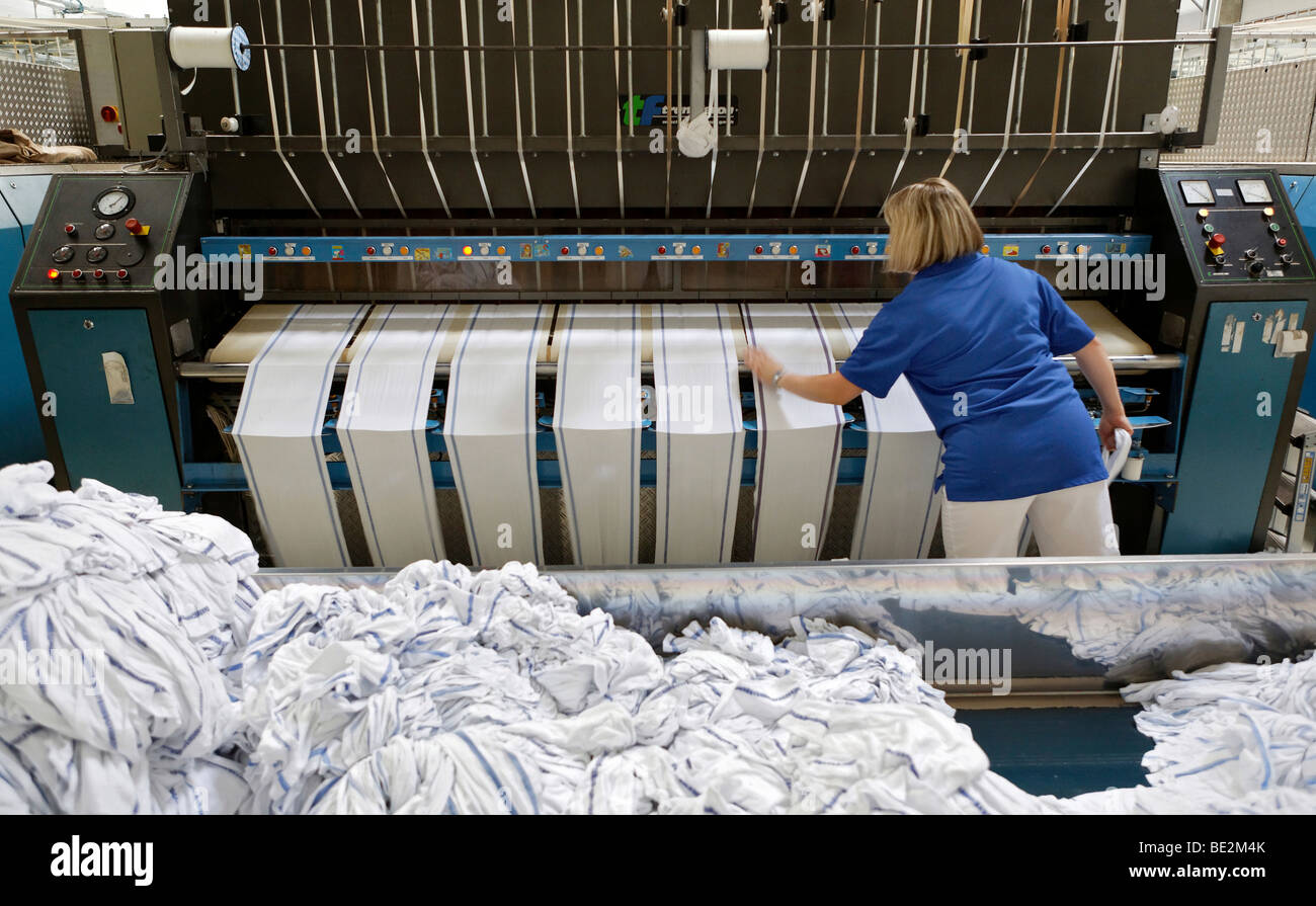 Janet Akgus working in the mangle hall at the handtowel rolls mangle machinery, Bardusch Uniform Rental & Laundry - Stock Image