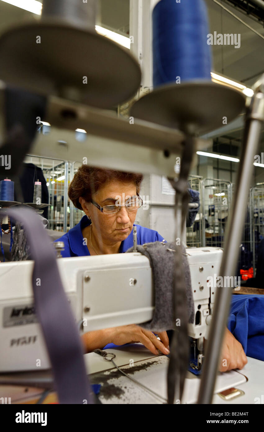Leyla Civi, employed for 36 years at Bardusch, sewing slightly damaged rental work clothing in the blue section - Stock Image