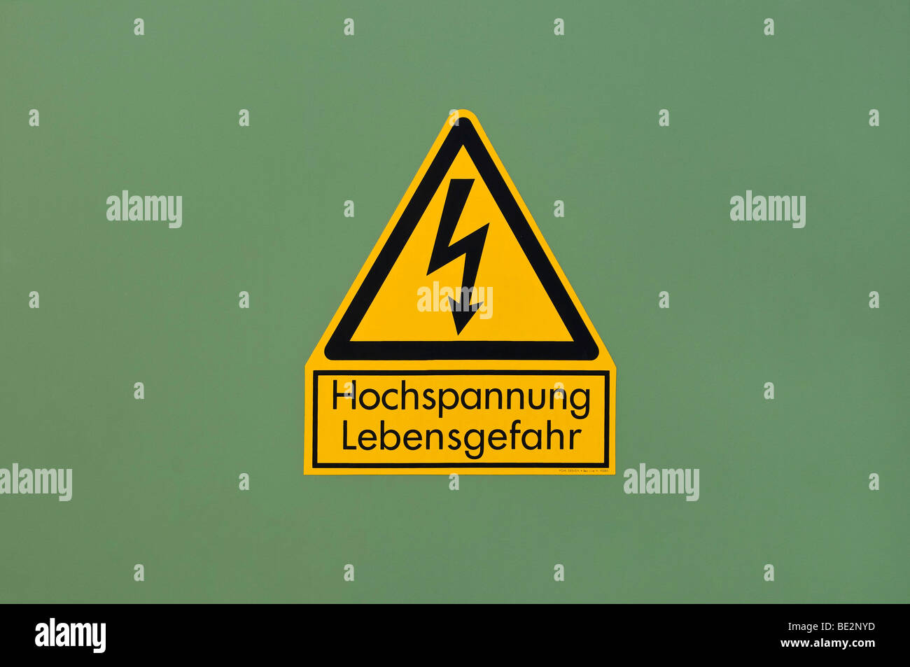 Yellow warning sign on green, high-voltage, danger - Stock Image