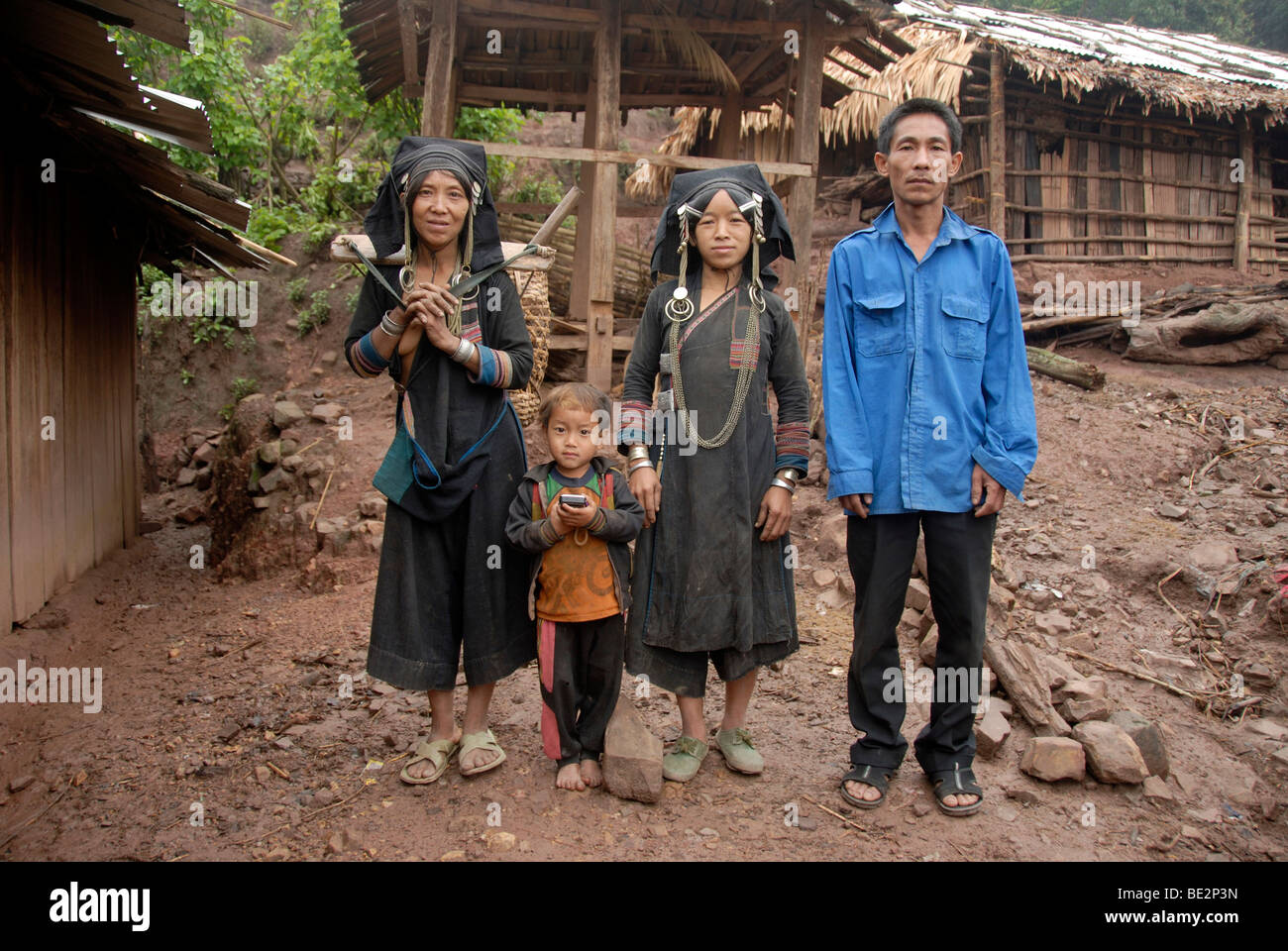 Poverty, portrait, ethnology, family of the Akha Pixor ethnic group in traditional dress, women, man, child, village - Stock Image