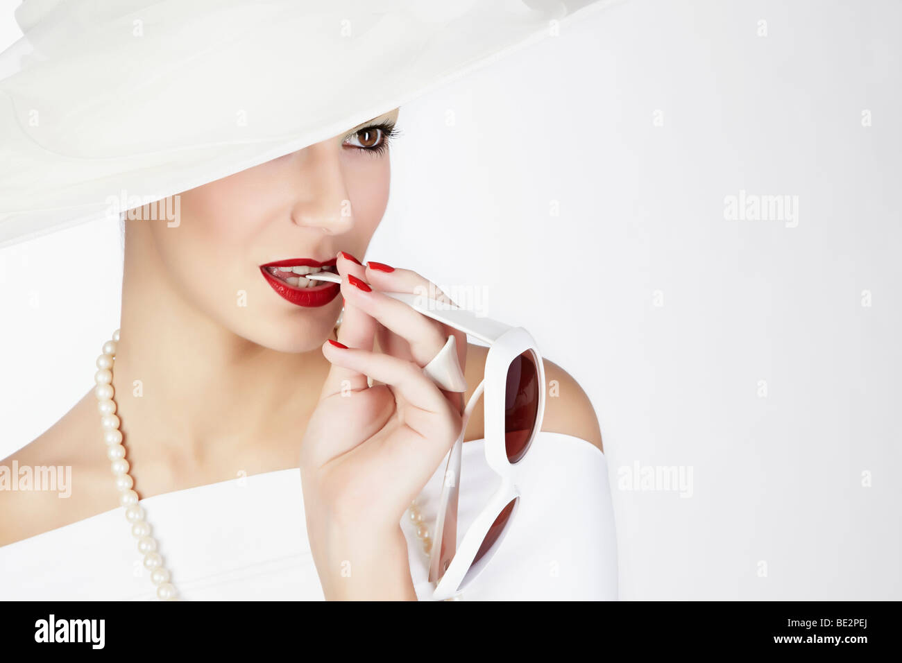 Portrait of a young woman wearing a white summer hat, a white dress and a pearl necklace, biting on the arm of a - Stock Image