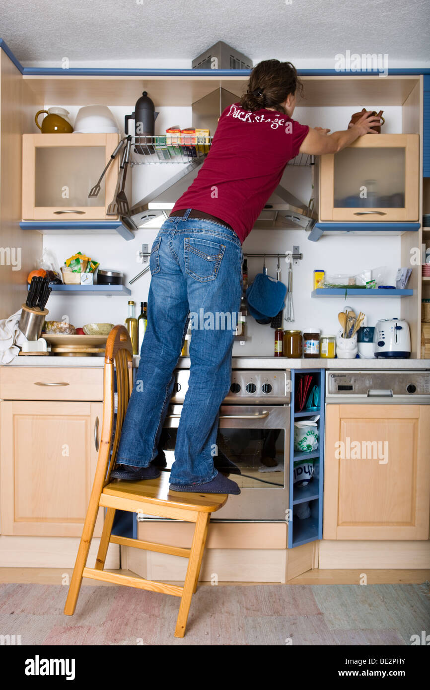 Household accidents, girl standing on a chair in the kitchen, tilting - Stock Image