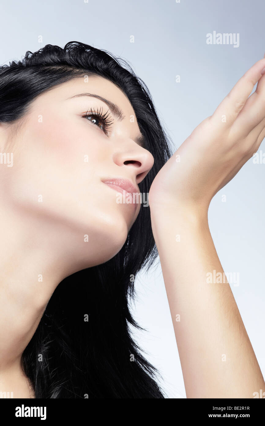 Young woman smelling perfume on her wrist, Beauty - Stock Image