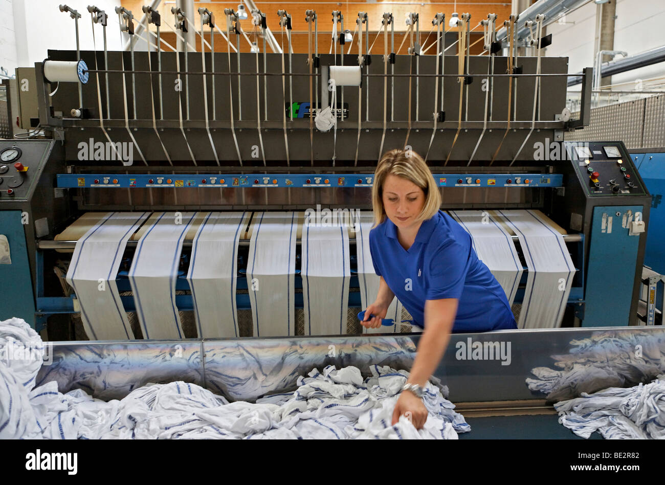 Janet Akgus working in the mangle hall at the handtowel rolls mangle machinery, Bardusch Uniform Rental & Laundry Stock Photo