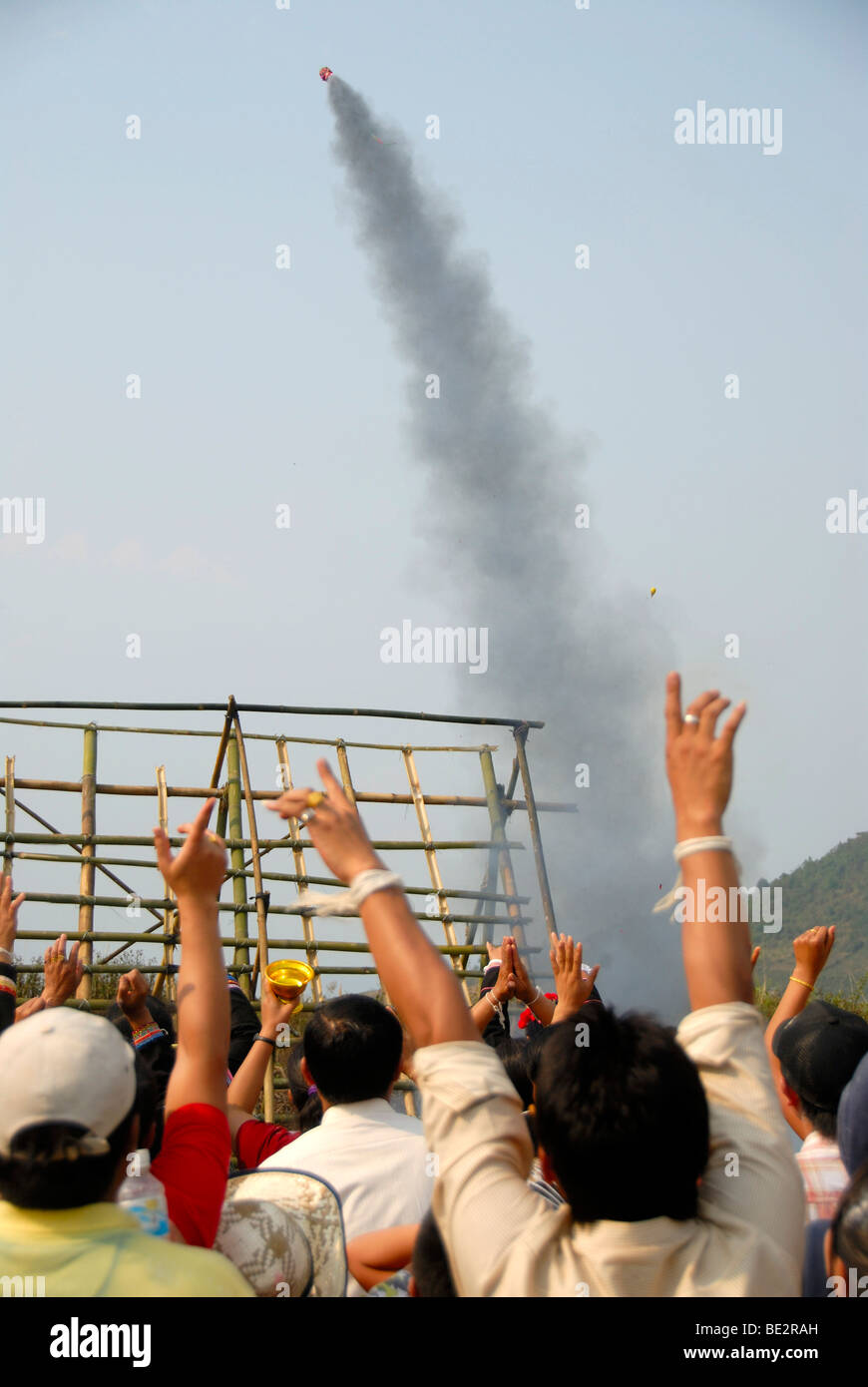 Rocket rising in the sky shortly after launch from a launch pad, cheering spectators, Pi Mai, Lao New Year festival - Stock Image