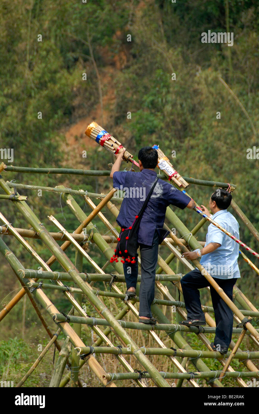 Men laying fireworks on a launching pad, Pi Mai, Lao New Year festival, city of Phongsali, Phongsali Province, Laos, - Stock Image