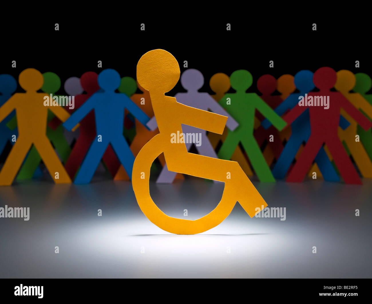 A disable paper figure stands under the spotlight on his wheelchair. - Stock Image