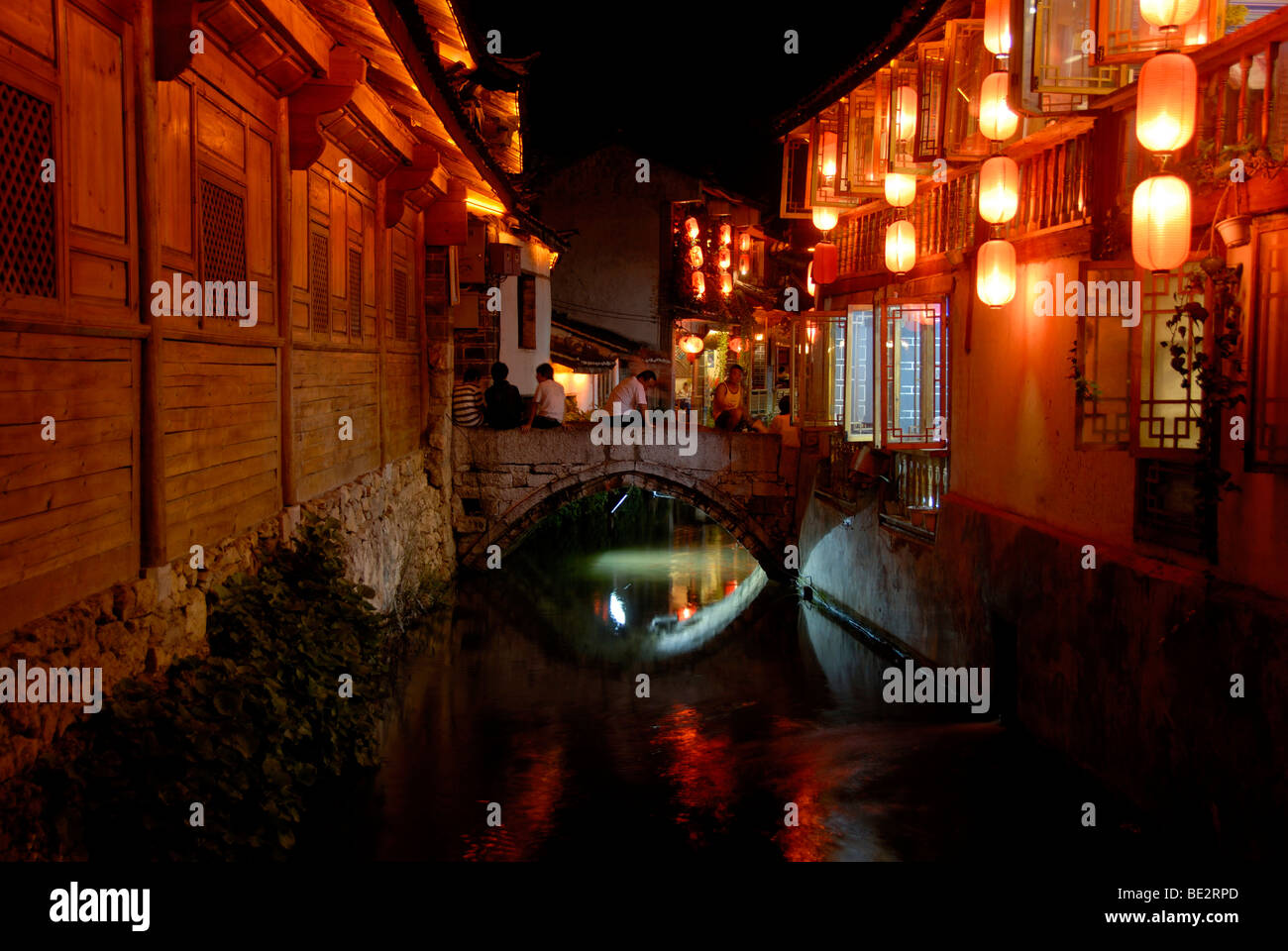 Old wooden houses, red lanterns, canal and bridge, historic centre of Lijiang, UNESCO World Heritage Site, night - Stock Image